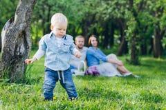 有两个孩子的家庭在夏天庭院里休息 库存图片