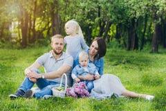 有两个孩子的家庭在夏天庭院里休息 库存照片