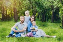 有两个孩子的家庭在夏天庭院里休息 免版税库存照片