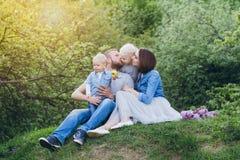 有两个孩子的家庭在夏天庭院里休息 免版税库存图片