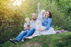 有两个孩子的家庭在夏天庭院里休息 免版税图库摄影