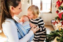 有两个孩子的年轻母亲圣诞节时间的 库存照片