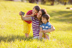 有两个孩子的愉快的母亲,拍照片在公园,室外 库存图片