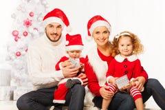 有两个孩子的愉快的年轻家庭圣诞节的 图库摄影