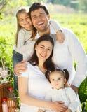 有两个孩子的愉快的年轻家庭户外 免版税库存图片