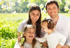 有两个孩子的愉快的年轻家庭户外 免版税图库摄影