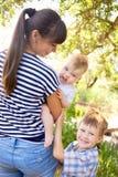 有两个孩子的愉快的年轻母亲 免版税库存图片