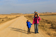有两个孩子的母亲在路旅行到山 免版税库存图片
