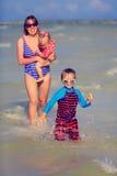 有两个孩子的母亲获得乐趣在夏天海 图库摄影