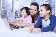 有两个孩子的爸爸使用膝上型计算机在家 免版税库存照片