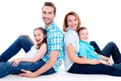 有两个孩子的白种人愉快的微笑的年轻家庭 免版税图库摄影