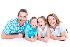 有两个孩子的白种人愉快的微笑的年轻家庭 免版税库存图片