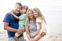 有两个孩子的美丽的家庭在海滩夏天 库存图片