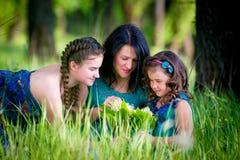 有两个孩子的美丽的少妇在公园 图库摄影