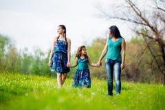 有两个孩子的美丽的少妇在公园 库存图片