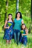 有两个孩子的美丽的少妇在公园 免版税库存图片