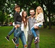有两个孩子的年轻愉快的家庭在夏天绿色公园 免版税库存图片