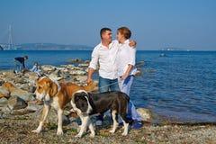有两个孩子,步行的两条大狗的愉快的家庭在海边 免版税库存图片