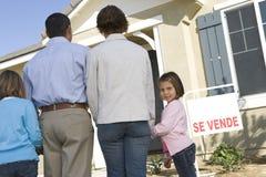 有两个孩子(6-8)的家庭在新房后面视图前面 免版税图库摄影