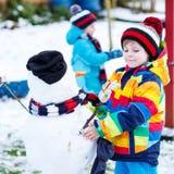 有两个小兄弟姐妹的男孩做雪人,演奏和fu 图库摄影