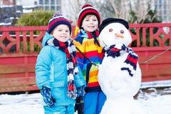 有两个小兄弟姐妹的男孩做雪人,演奏和fu 免版税库存照片