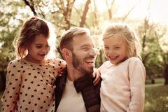 有两个小女儿的唯一父亲在公园 免版税库存图片