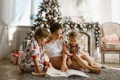 有两个小女儿的年轻美丽的母亲坐地毯并且在与礼物的新年的树附近读了书 图库摄影