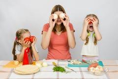 有两个小女孩的妈咪获得乐趣在使用与菜的厨房用桌上 库存图片