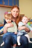 有两个幼儿的被注重的母亲婴孩小组的 图库摄影