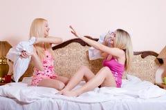 有两个性感的白肤金发的女孩在床上的乐趣战斗的枕头在他们上的轻的拷贝空间背景 免版税库存图片