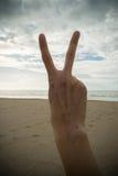 有两个手指的手在和平或胜利 库存照片