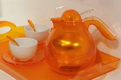 有两个杯子和塑料橙色匙子的橙色透明设计茶壶在橙色塑料盘子 免版税图库摄影