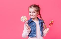 有两个棒棒糖的十几岁的女孩 库存图片