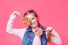 有两个棒棒糖的十几岁的女孩 免版税库存照片