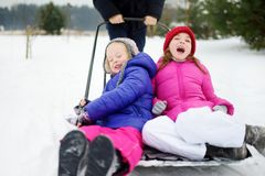有两个滑稽的妹在雪铁锹的乘驾在冷颤的冬日 使用在雪的孩子在冬天期间打破 免版税库存图片