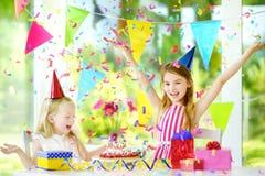 有两个滑稽的妹生日聚会在家,吹在生日蛋糕的蜡烛 库存图片