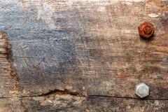 有两个生锈的螺栓的木棕色老委员会 在树的镇压,火踪影  免版税库存照片