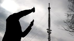 有两个电话的一个人寻找在电话塔,一个坏信号的背景的一个付得起的网络 股票录像
