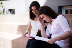 有两个的女学生困难时期,一起为检查做准备户外 免版税库存图片