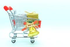 有两个礼物盒和金铃的唯一购物车 图库摄影