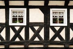 有两个窗口的半木料半灰泥的墙壁 库存图片