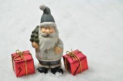 有两个红色小包的圣诞老人在雪背景,水平 免版税库存照片