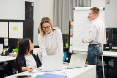 有两个美丽的办公室工作者交谈,当人同事图画在活动挂图时的经营战略 库存图片