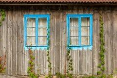 有两个蓝色窗口的木墙壁 库存图片