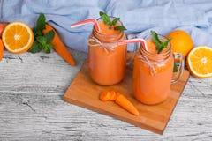 有两个金属螺盖玻璃瓶的一个木板有薄菏红萝卜圆滑的人、蓬蒿、桔子和叶子的在轻的背景的 免版税图库摄影