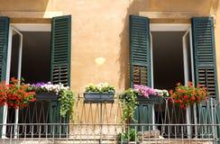 有两个门的阳台打开和五颜六色的花 免版税库存图片