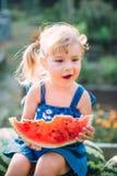 有两个马尾辫的吃西瓜的美丽的白肤金发的女孩画象  免版税库存图片