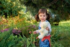 有两个马尾辫的小愉快的女孩 美丽的小女孩吃糖果 免版税库存图片
