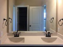 有两个水槽的新的在墙壁上的卫生间和镜子 免版税图库摄影