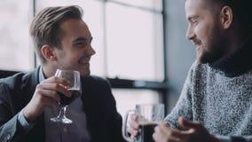 有两个年轻的人耍笑和一次活跃讨论,在客栈做多士和高兴地喝啤酒 庆祝 股票录像